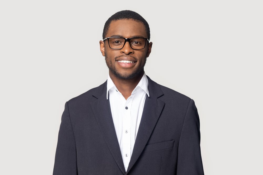 Smiling,African,American,Millennial,Businessman,In,Glasses,Isolated,On,Grey